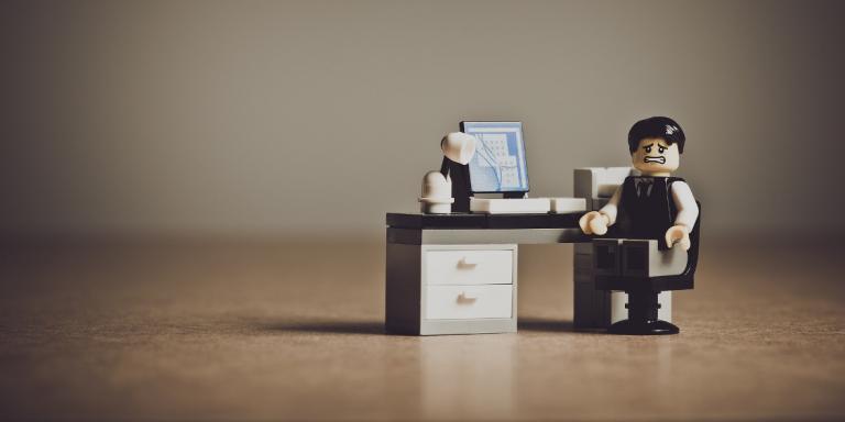 Unzufriedenes Lego Männchen am Arbeitsplatz