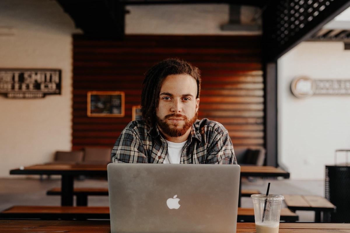 Mann vor Laptop in Café